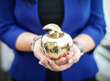 Woman holding the Golden Apple Award | Ways To Give: Support An Event