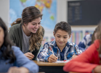 Teacher helping a student | Ways To Give: Give from Your IRA